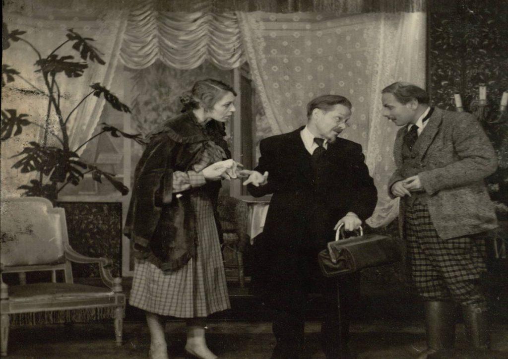 Pinigėliai. 1953. Scena iš spektaklio Raudonauskienė – akt. I.Gurinaitė, Raudonauskis – akt. V.Tautkevičius, Mikšas – akt. A.Puzanauskas